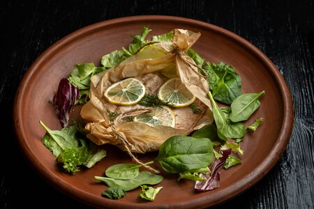 Fish cocked in a wrapper with herbs and sliced lemon.