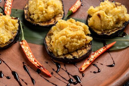 Pumpkin puree is laid out on grilled eggplant.