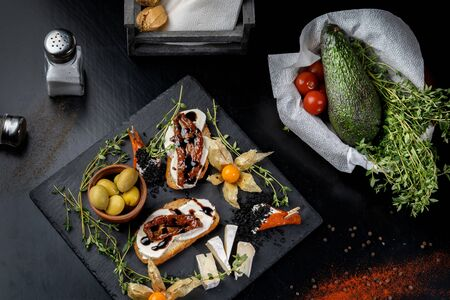 Snacks are laid out on black slate, physalis, salami, cheese and sun-dried tomatoes.