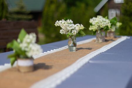 The path to the wedding arch is decorated with bouquets of white sirens in bottles. Stock Photo