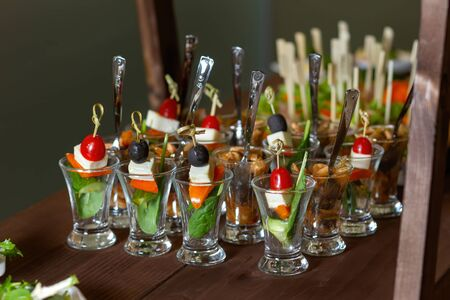 A table with catering cups with teaspoons..