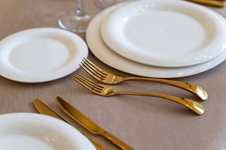 Chic and elegant, gold-plated cutlery and white plates, table setting with empty plates. Luxury restaurant, preparation for the celebration. Clouse-up.