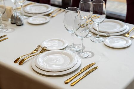 Chic and elegant, gold-plated cutlery and white plates, table setting with empty plates. Luxury restaurant, preparation for the celebration. Beautiful glasses and wine glasses. Clouse-up. Reklamní fotografie