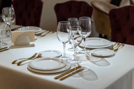Chic and elegant, gold-plated cutlery and white plates, table setting with empty plates.