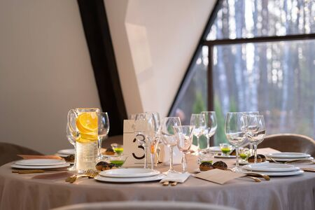 Chic and elegant, gold-plated cutlery and white plates, table setting with empty plates. Luxury restaurant, preparation for the celebration. Beautiful glasses and wine glasses Reklamní fotografie