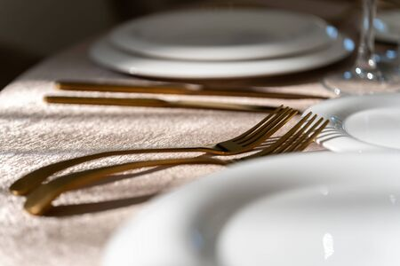 Chic and elegant, gold-plated cutlery and white plates, table setting with empty plates. Luxury restaurant, preparation for the celebration. Macro. Reklamní fotografie