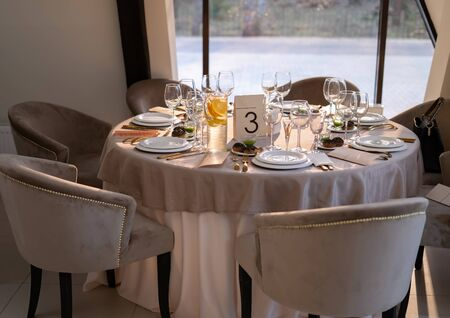 Chic and elegant, gold-plated cutlery and white plates, table setting with empty plates. On the table is an orange lemonade. The table opposite the window.