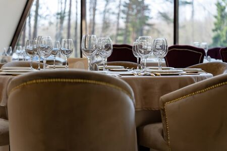 Beautiful table setting with glasses, plates and napkins. Visible outlines of trees outside the window. General form.