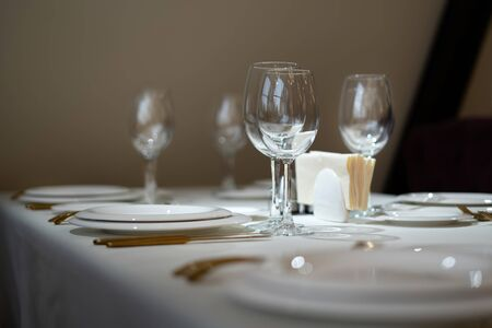 Chic and elegant, gold-plated cutlery and white plates, table setting with empty plates. Glasses in the light from the window. Side view. Reklamní fotografie