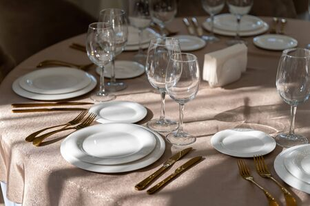 Chic and elegant, gold-plated cutlery and white plates, table setting with empty plates. Luxury restaurant, preparation for the celebration.