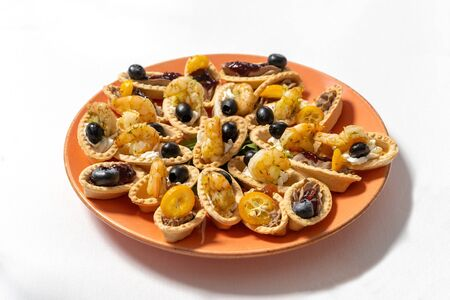 Tartlets with cream cheese, shrimps and black olives, decorated with kumquat.