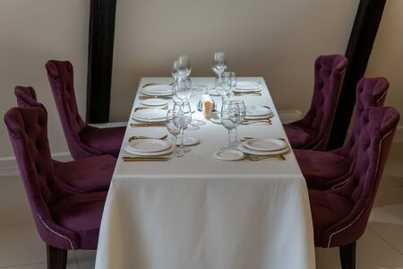 Chic and elegant, gold-plated cutlery and white plates, table setting with empty plates. Luxury restaurant, preparation for the celebration. Beautiful glasses and wine glasses. Front view.