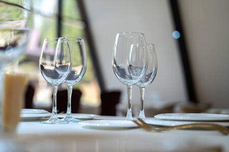 Chic and elegant, gold-plated cutlery and white plates, table setting with empty plates. Glasses in the light from the window. Side view.