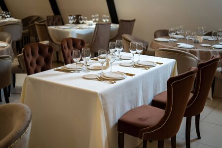 Chic and elegant, gold-plated cutlery and white plates, table setting with empty plates. Beautiful armchairs and a fully covered table.