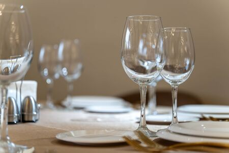 Chic and elegant, gold-plated cutlery and white plates, table setting with empty plates. Glasses in the light from the window-2. Reklamní fotografie
