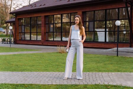 Young pretty sexy girl in a gray pants and a silver blouse. The gaze is directed down.