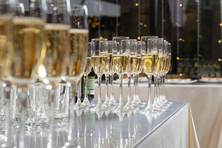 Row of glasses filled with champagne, a beautiful catering party.