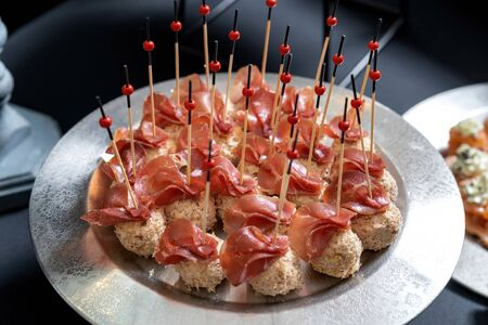 Cheese balls sprinkled with grated almonds, covered with jamon. Banco de Imagens