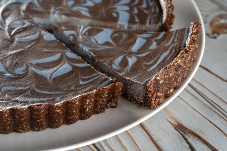 Chocolate cake with nuts, laid on a plate. Beautifully cut piece. Wooden brushed background.