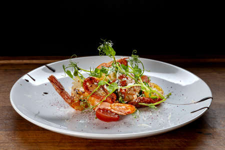 Prawn salad. Healthy Shrimp Salad with mixed greens and tomatoes, the food glows in a beautiful backlight.