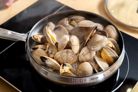 Fresh raw clams lie in a skillet on an electric stove. Cooking delicious food. Standard-Bild