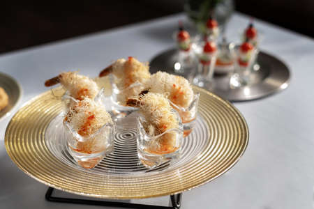 Shrimps wrapped in wheat thread and baked. Catering, beautiful table. Silver designer plate. Standard-Bild