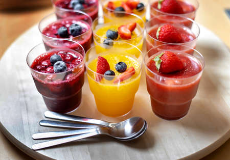 Berries jam in glass cups with blueberries, strawberries, cherries.