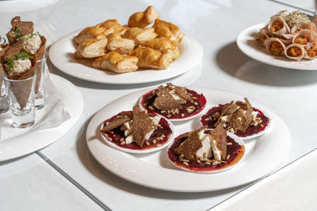 Luxurious catering table. Croutons with cheese and jam, decorated with seeds.
