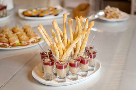 Luxurious catering table. Breadsticks sprinkled with white sesame seeds. Snacks in glasses. Standard-Bild