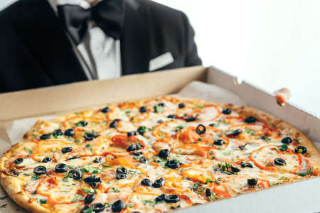 A man in a suit and bow tie holds a box of pizza in his hands.