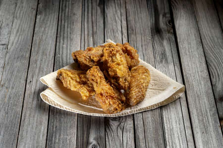 Delicious barbecue chicken wings, on a rustic wooden background.