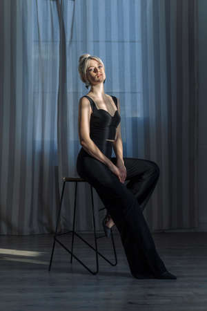 Close up studio portrait of a pretty blonde woman in black top and black pants. Standard-Bild