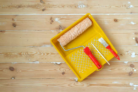 Yellow painting tray cuvette and paint roller with red handle, made of synthetic fiber.