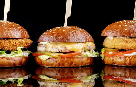 Delicious hamburgers served on black background. Burgers with different fillings, fish chicken, chickpeas.