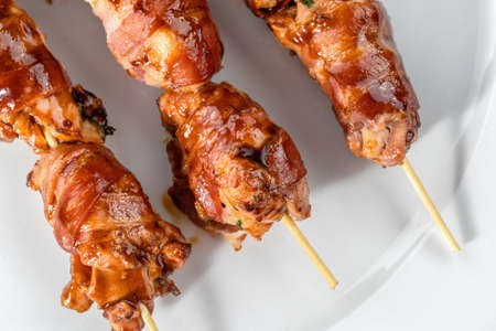 Grilled bacon-wrapped chicken tenders are laid out on a white plate. Strung on wooden skewers-2.