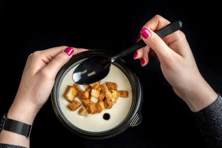 Cream soup with croutons. Delicious mushroom, top view, girl with a spoon. Reklamní fotografie