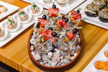 Colorful canape on skewers with sausage and fried egg toast. Tasty appetizer for a party or banquet.