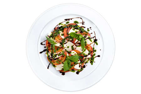 Slices of mozzarella and tomato, with fresh basil and capers sauce.