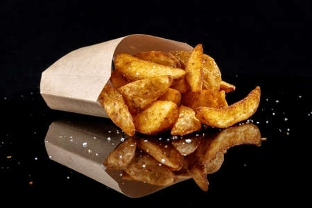 Fried potato wedges spilled out of a paper bag.