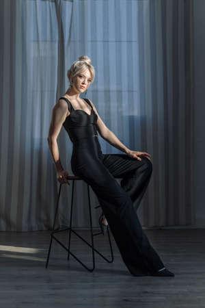 Close up studio portrait of a pretty blonde woman in black top and black pants. Reklamní fotografie