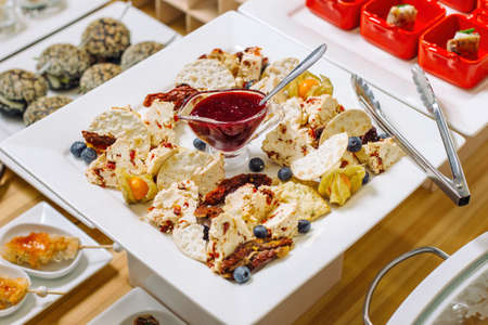 A delicious selection of cheese platter made from homemade cheese varieties. With a bowl filled with jam.