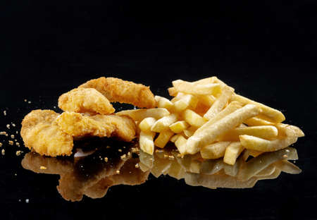 Image of the fried chicken and deep-fried fish pieces. is a best food. Laid out on a black mirror Reklamní fotografie