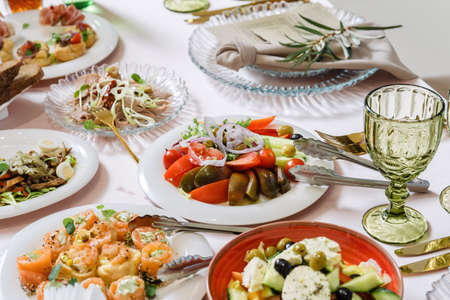 Vegetable salad, tomatoes, cucumbers. The table is lined with dishes. Beautiful dishes, luxury catering.