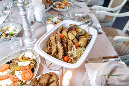 Meat with potatoes and onions, in a white food warmer. Beautiful festive table.