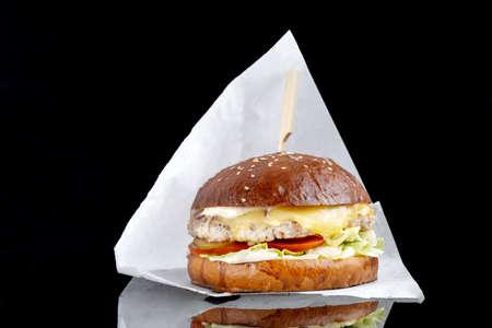 Delicious hamburger served on black background. Black mirror surface. Close-up Reklamní fotografie