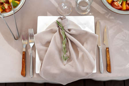 Table setting, luxury catering. Forks, knives, decorated with a sprig of rosemary.