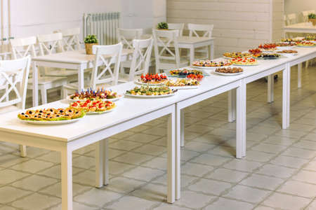 White wooden table covered with catering service. Minimalist design. Reklamní fotografie