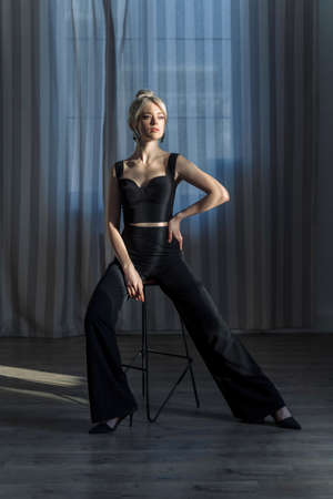 Studio portrait of a pretty blonde woman in black top and black pants, looking to the side.