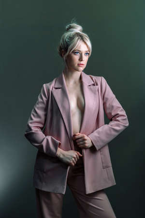 Sexy young blonde, a jacket dressed on a naked body. The model is looking to the side. Reklamní fotografie