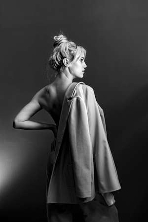 Portrait, softbox is visible in the frame. Sexy young blonde looking standing topless, a jacket hanging on his shoulder.